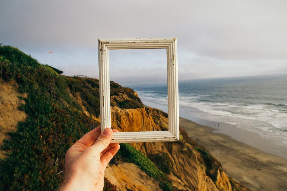 hand holding up empty wooden picture frame toward a hilly landscape