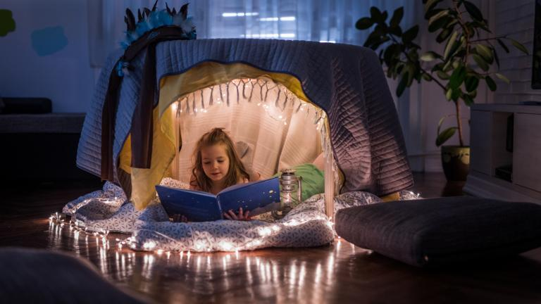 Small girl relaxing inside of a tent at home and enjoying while reading a book.