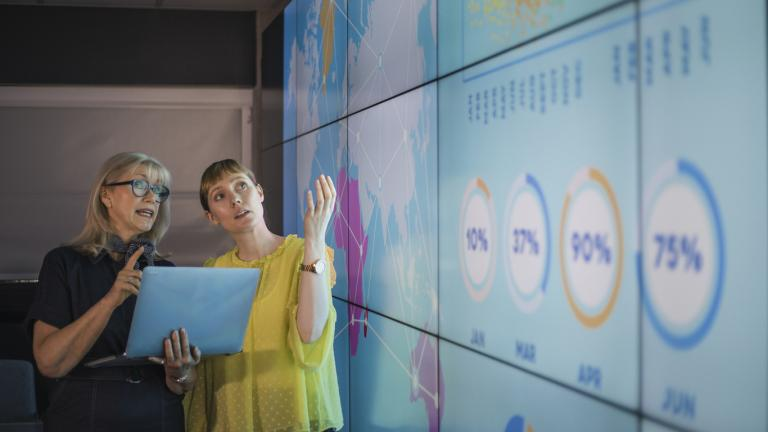 An experienced woman mentors a female colleague, the mature woman is holding a laptop as they debate data from an interactive display