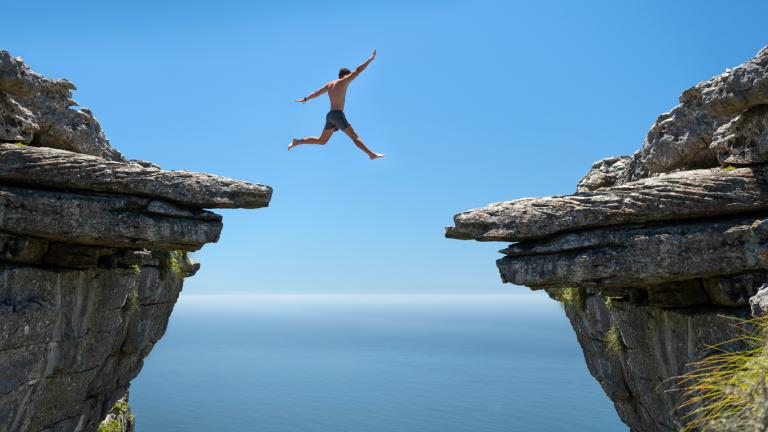 man jumping over a gap between two cliff faces