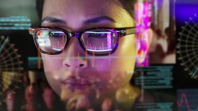 Close up stock photo of an Asian woman carefully studying moving data on her computer screen, the screen is unusual as it is transparent and the camera is looking through the back of the screen.