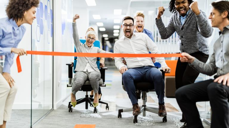 Cheerful business team having fun during chair race in the office.