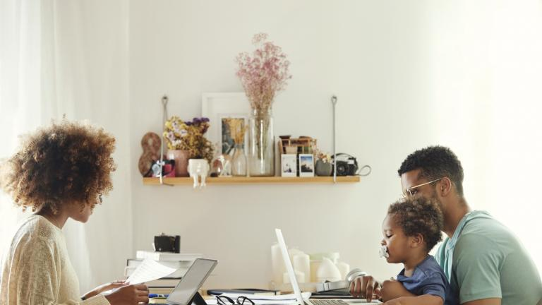 Mother using digital tablet for working from home. Father using laptop with son at table. They are sitting in kitchen.