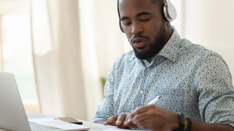 Concentrated young african american man in headphones listening to online university lectures, writing down notes.