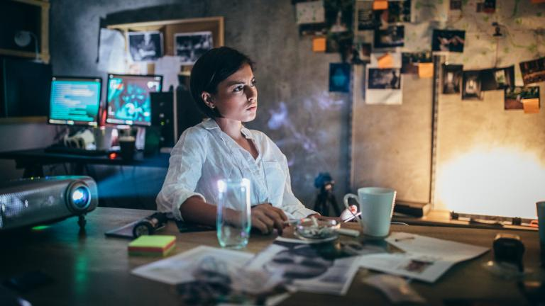 Female FBI agent/policewoman working late in the office. Criminal investigation concept