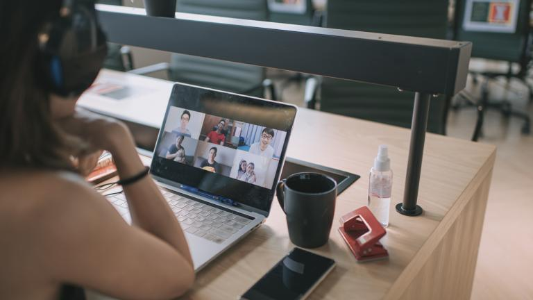 woman having video conference call with her business partners in coworking office