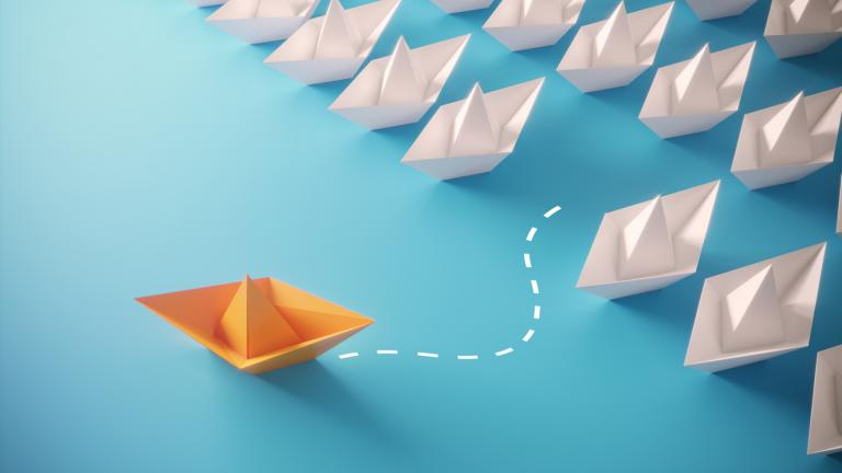 White paper boats and orange colored one standing out from the crowd, can be used leadership/individuality concepts.( 3d render )
