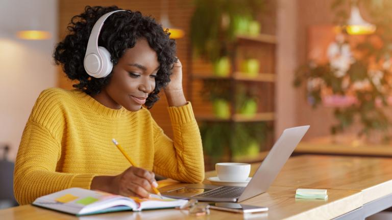 Smiling black girl with wireless headset studying online, using laptop at cafe, taking notes, copy space