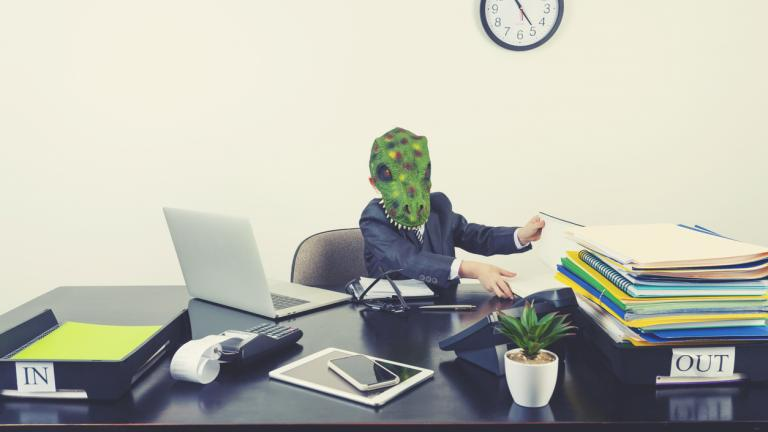 Young boy dressed in a suit working at a large desk. He is wearing a monster dinosaur mask and looks very scary and intimidating.