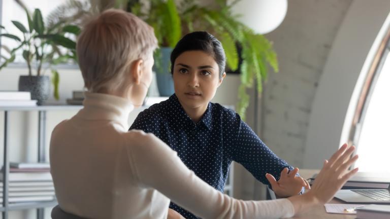 businesswomen negotiating sit at desk in office
