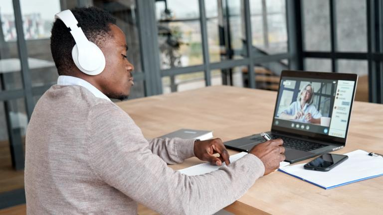 Serious african business man or black male student wearing headphones conference video calling, watching webinar online, social distance learning or working using laptop at home office, taking notes.