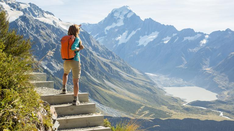 Hiker stands on a mountain top and looks at view. Mount Cook on the background, New Zealand.