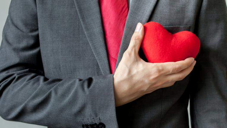 Businessman showing compassion holding red heart onto his chest