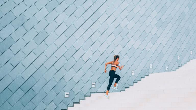 Woman exercising on a staircase outside in the city.