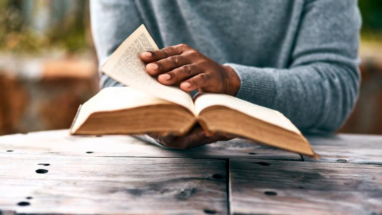 Cropped shot of an unrecognizable man reading a book
