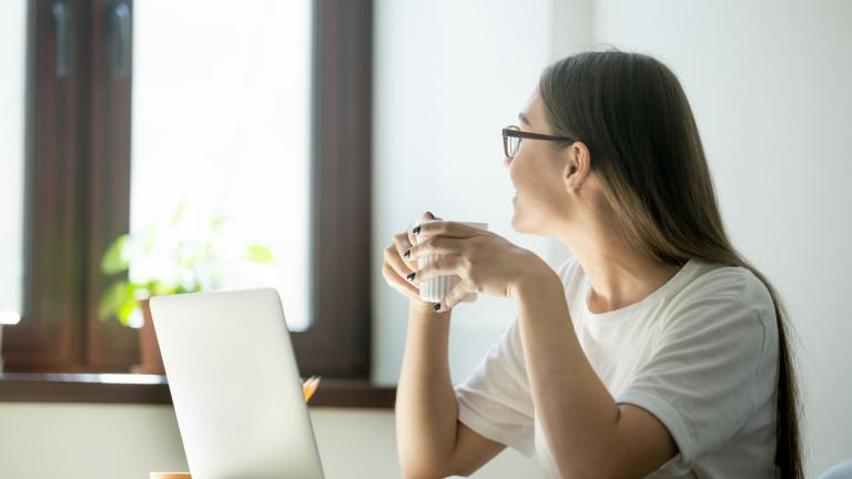 Smiling woman looking in window having work break