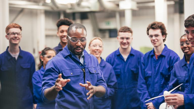 diverse group of apprentices being taught by an instructor