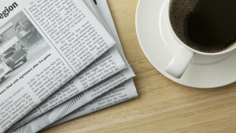 A cup of coffee and the papers