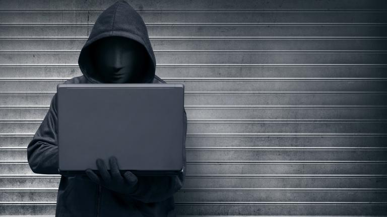 Feedback given anonymously: masked worker typing on laptop