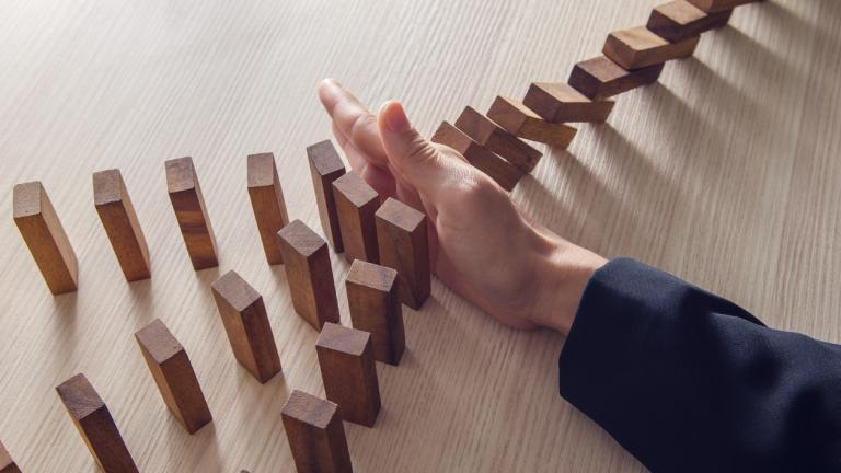 hands stopping dominoes falling