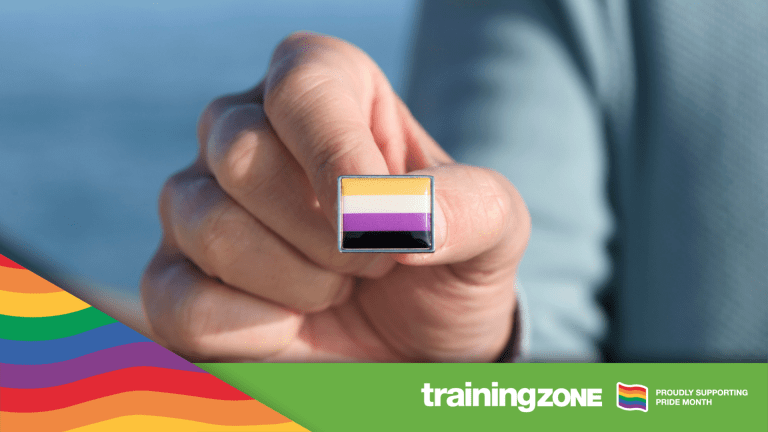 closeup of a young caucasian person showing a lapel pin patterned with a non-binary pride flag