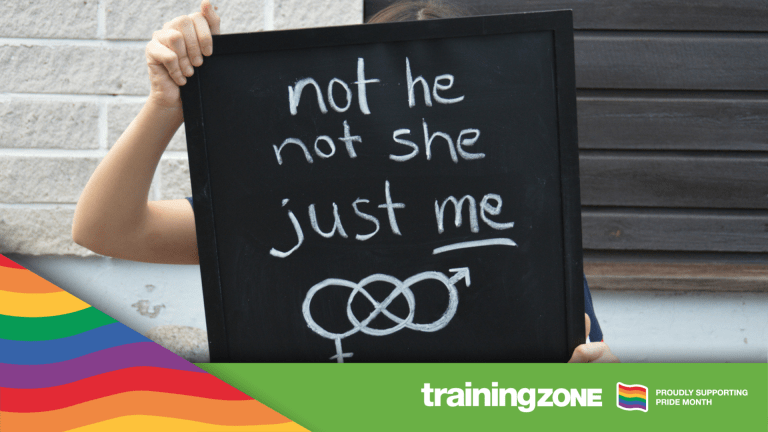 Teenager identifying as non-binary is holding a black signboard with handwritten text and symbol related to gender identity