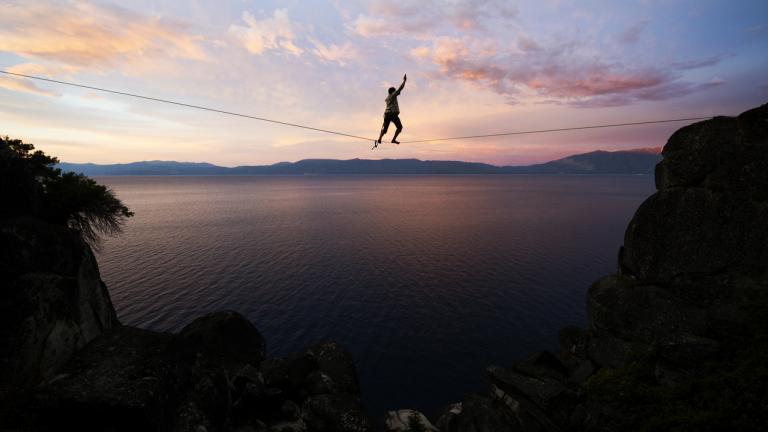 Man walking across tightrope