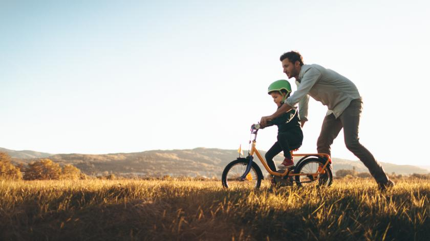 Father teaching son to ride a bike