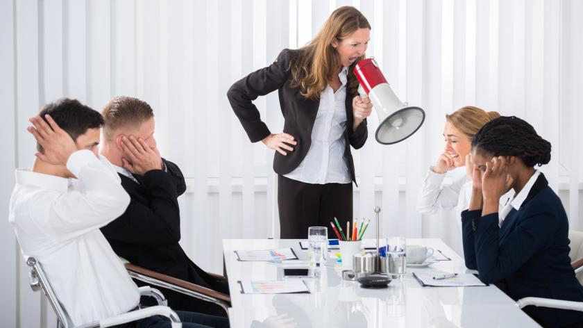 Business woman shouting with megaphone in meeting