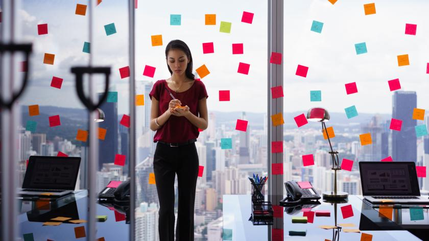 Woman covering office in post-it notes