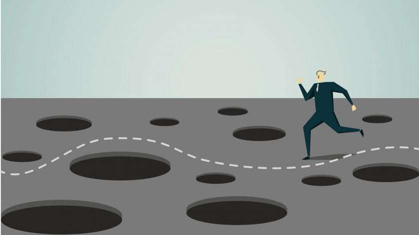 Businessman dodging holes in the ground graphic