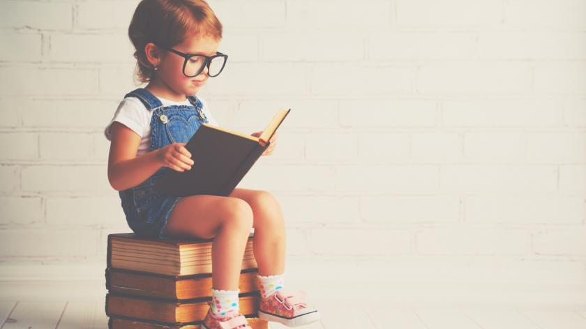 little girl with glasses reading books