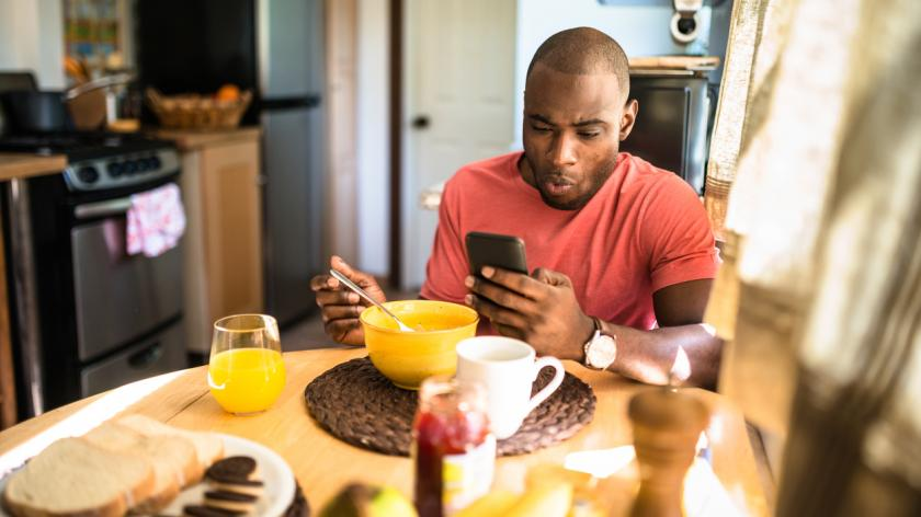 man eating breakfast checking his phone