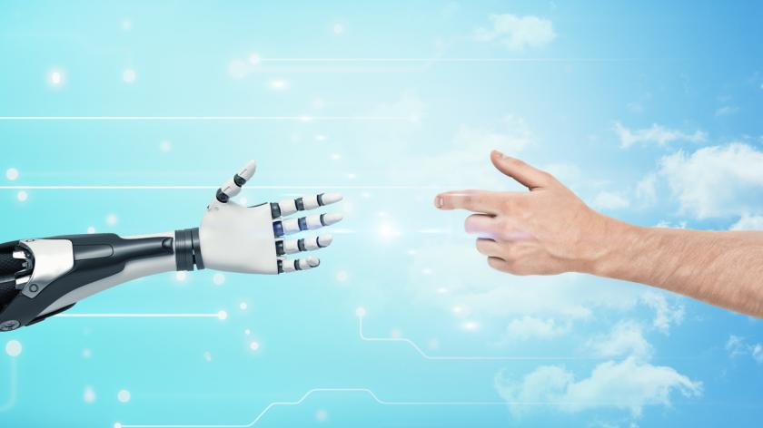 A human hands reaches to the white and black very detailed robotic hand on blue background