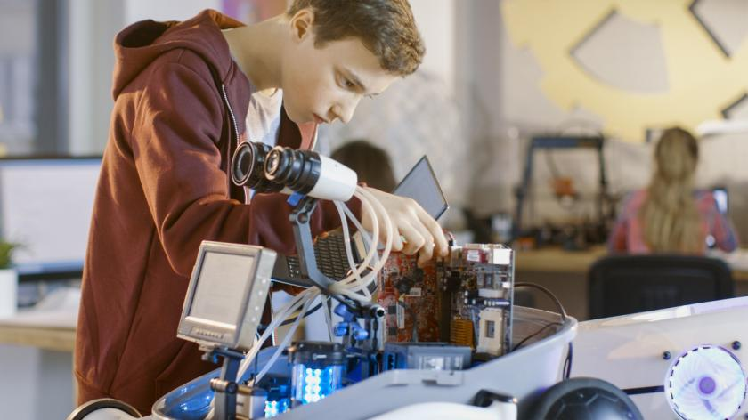 Boy Works on a Fully Functional Programable Robot in Classroom