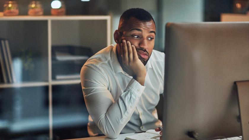 man staring at computer procrastinating
