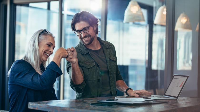 Young businessman and senior businesswoman making a fist bump at office. Business colleagues looking happy and excited after completion of project.