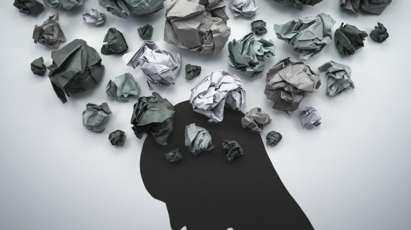 Concept image of anxiety and negative emotion. Waste paper and head silhouette.