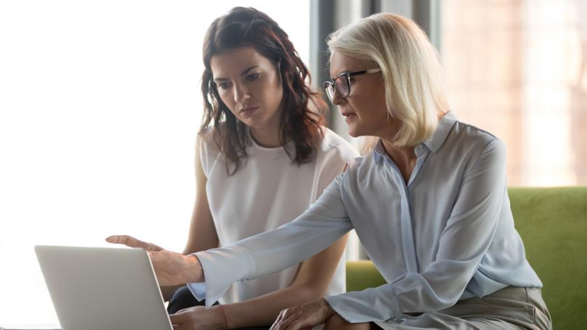 Serious middle aged executive manager explaining colleague online work together pointing at laptop