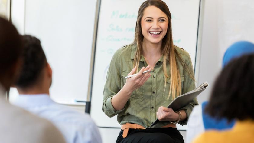 A smiling young female creative professional sits on a stool before a group of employees. She gestures as she speaks to a new employee training class.
