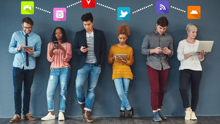 Full length shot of a group of creative businesspeople standing in a line and using their digital devices at work