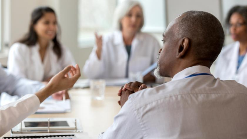 Mature male hospital administrator listens to concerns during a conference with medical staff.