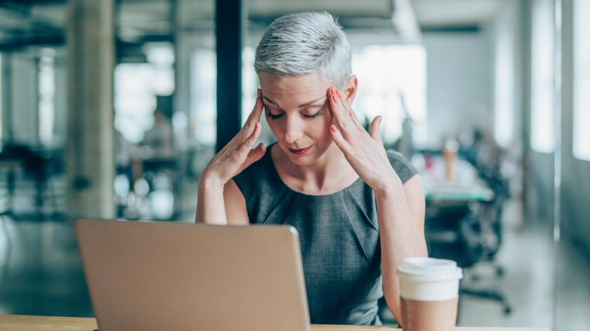 Shot of a stressed businesswoman with headache in the office