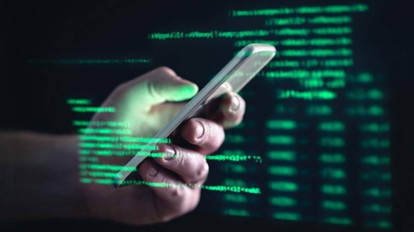 Hacker with cellphone. Man using dark web with smartphone.