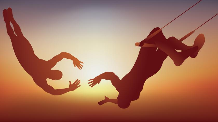 trapeze artists attempting a catch mid air