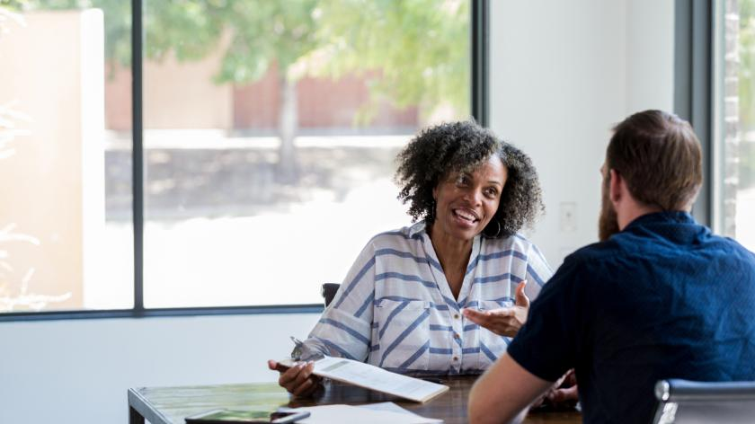 Mature female counselor gestures during a conversation with a young male client.