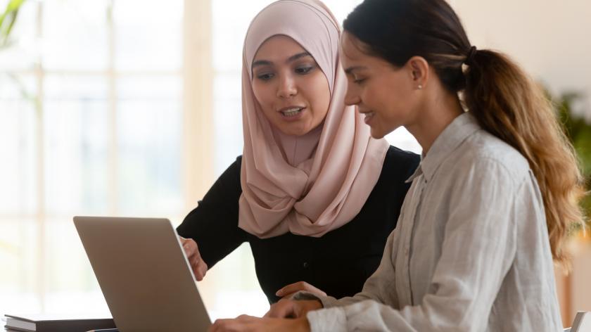 Focused asian muslim female mentor teacher teach caucasian intern worker learning new skills explaining computer software work together at modern workplace, apprenticeship internship course concept
