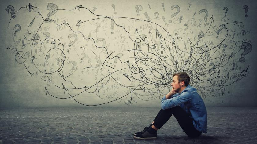man sitting next to illustrations doodled near his head illustrating the concept of poor mental health