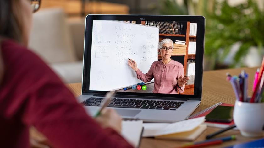 Young student watching lesson online and studying from home. Young woman taking notes while looking at computer screen following professor doing math on video call.