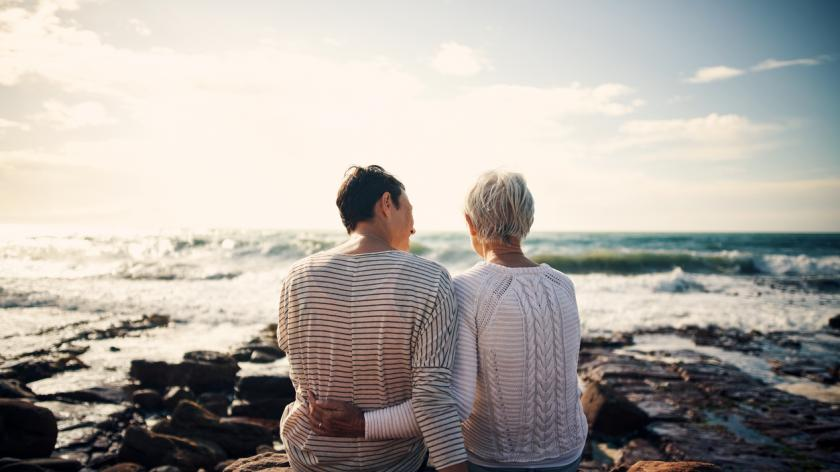 Rearview shot of a senior woman bonding and spending time with her adult daughter at the beach
